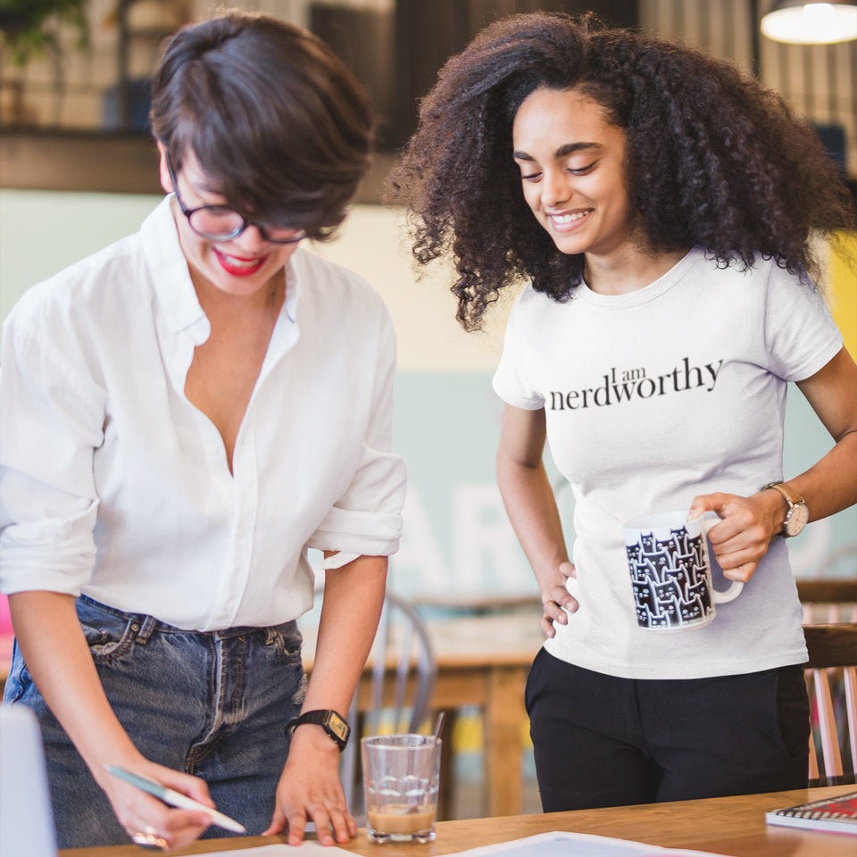 "Two women standing over a table. One of them is wearing a ""I am nerdworthy"" tshirt."