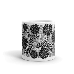 front of 11oz white mug with black flowers on top of circuit background