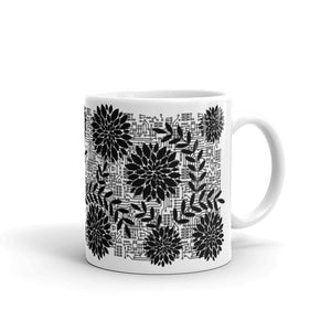 right side of 11oz white mug with black flowers on top of circuit background