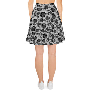 back side of white skater skirt with a pattern of black flowers on top of circuit background