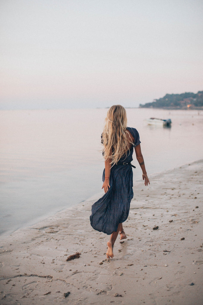 Woman barefoot on the beach wearing a spring capsule wardrobe piece - a midi dress