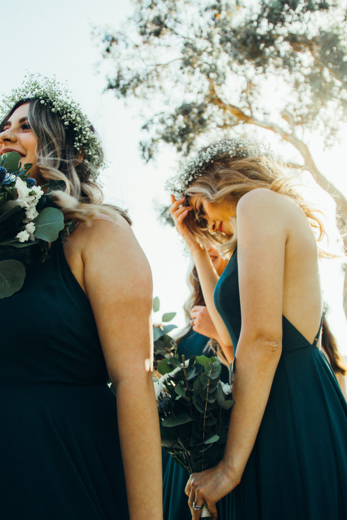 two women as bridesmaids wearing bridesmaid jewellery and carrying flower bouquets
