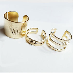 The set of three Kelabu chunky stacking rings in Gold set out in a line on a plain white background