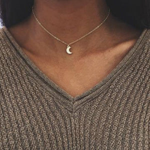 Woman wearing the dainty moon pendant necklace in Gold with a v-cut khaki coloured chunky knit jumper