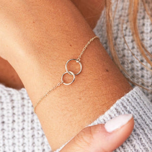 Woman wearing the Double Karma circle gold boho bracelets with a soft grey knitted jumper and matching painted nails