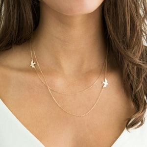 The gold Kelabu double layer necklace with beautiful bird charm worn by a woman with long brown curled hair wearing a white t-shirt