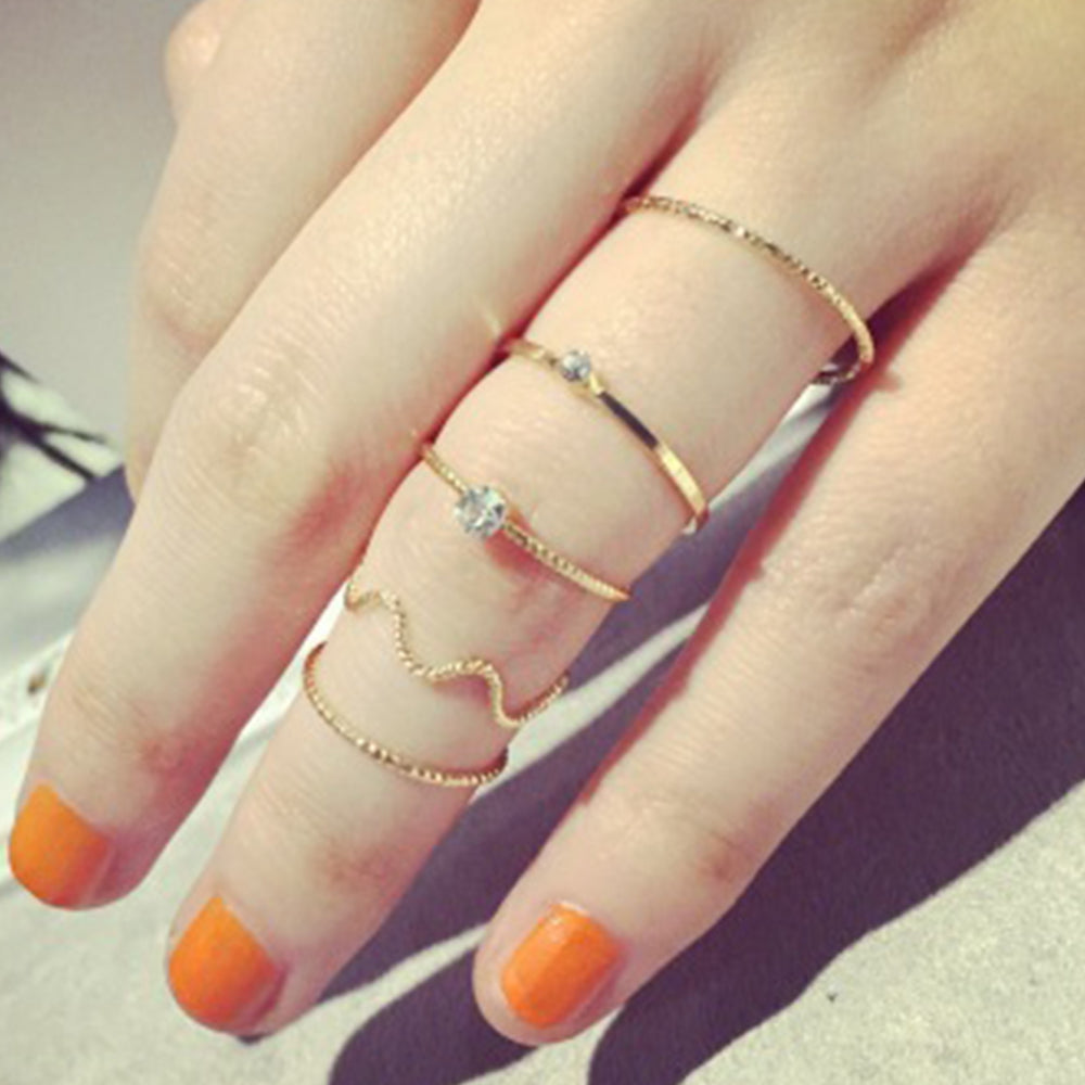 The Kelabu simple stacking rings being modelled by a woman wearing them all on one finger with her nails painted a bright orange colour