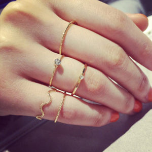 The Kelabu simple stacking rings being modelled by a woman wearing them on different fingers with her nails painted a bright orange colour