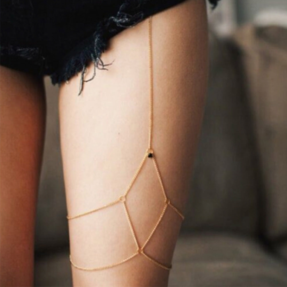Woman wearing the gold Kelabu diamond detail leg chain underneath ripped black denim shorts