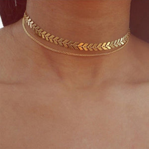 A woman wearing the Kelabu gold choker necklace which features two different designs and is multi layered