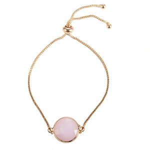 Our beautiful Kelabu beaded tie bracelet with gold chain and pink pendant on a plain white background
