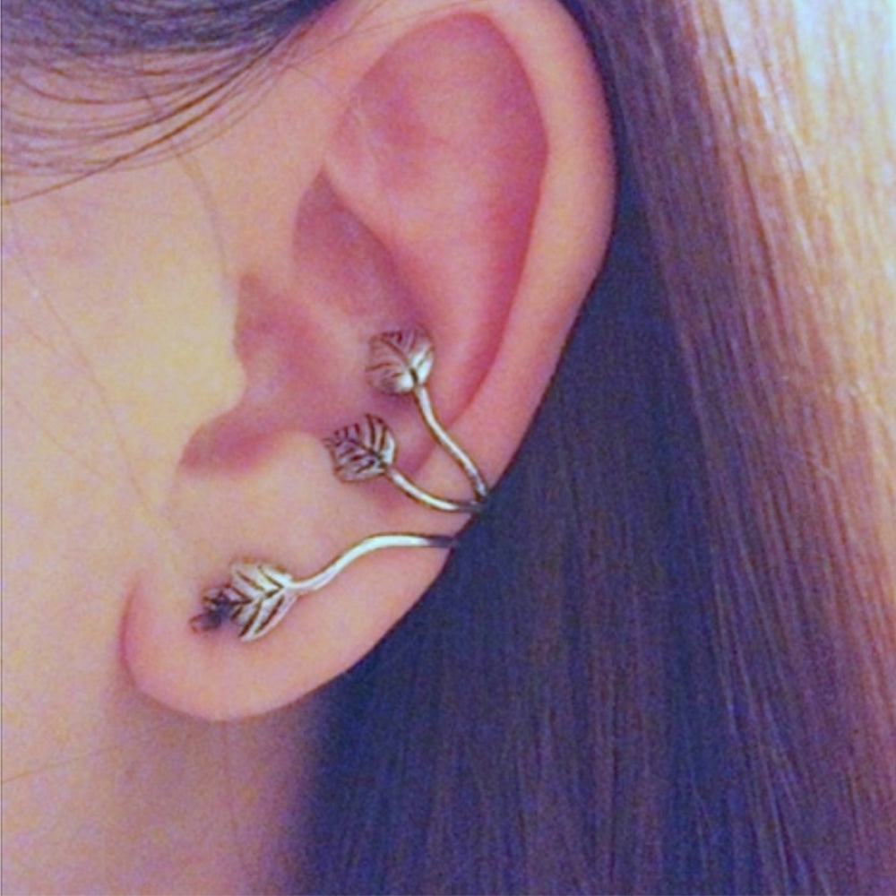 The silver ear crawler cuff from Kelabu shown being worn by a woman with long brown hair tucked behind her ears
