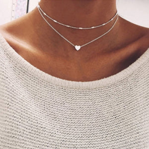 Woman wearing the silver heart charm necklace set with a cream jumper on