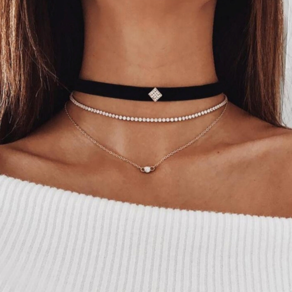 The stylish layered choker from Kelabu, with velvet, gold and crystal designs, being worn by a woman with long brown hair and wearing an off the shoulder white jumper