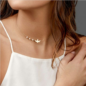 Our gold bird charm choker necklace being styled by a woman wearing a stylish white vest top and curled long brown hair