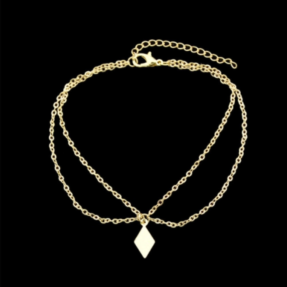 Gold Kelabu bohemian anklet laid flat on a black background