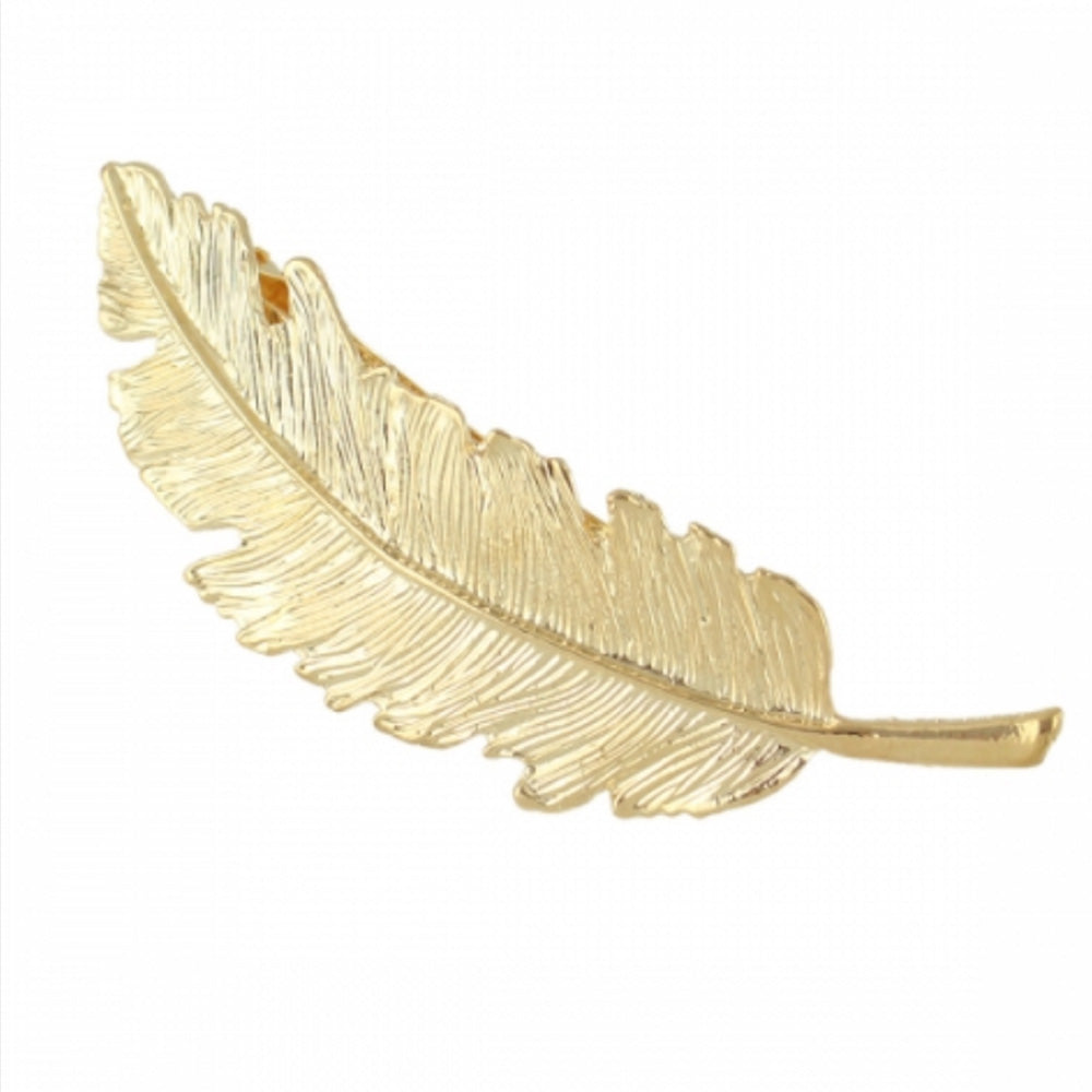 The Kelabu gold feather hair clip on a plain white background