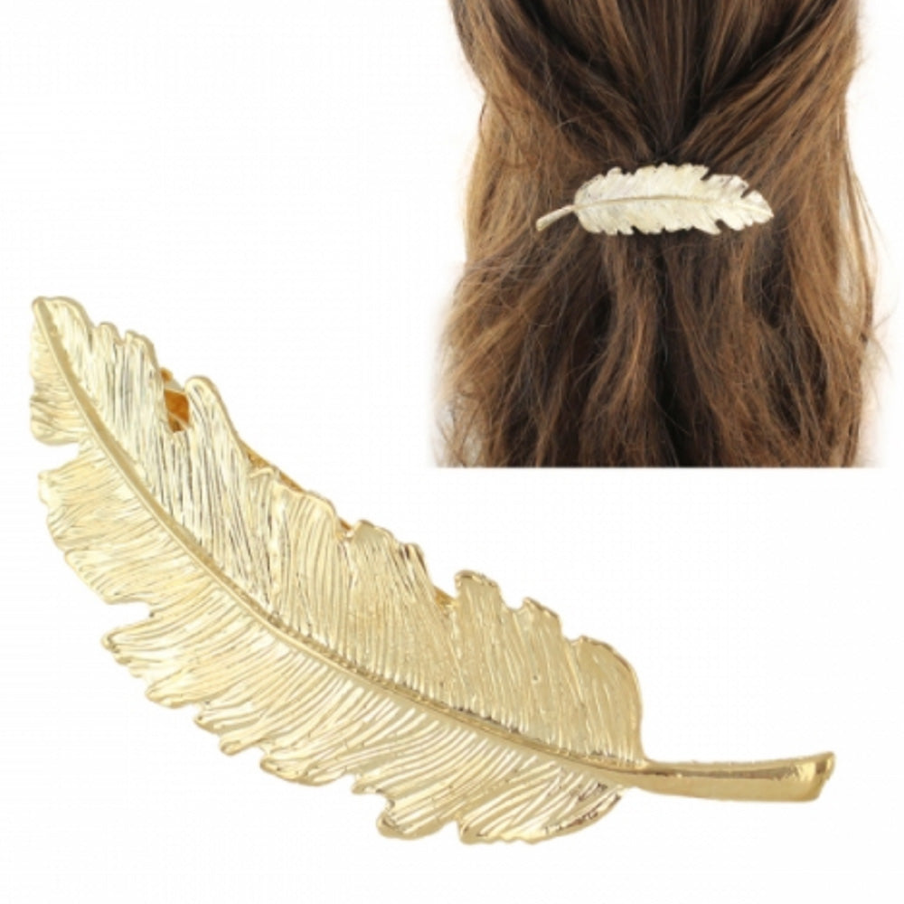 Woman with her brown hair tied back styling the gold feather hair clip by Kelabu