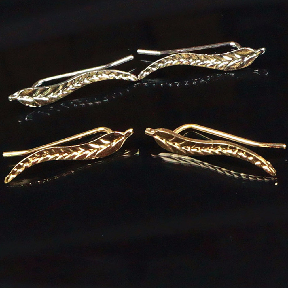 Gold and silver Kelabu bohemian crawler leaf shaped earrings on black background