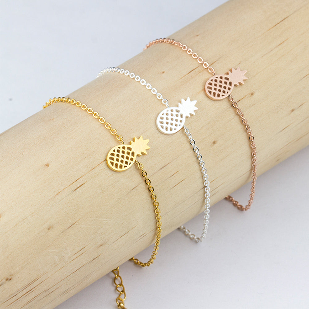 All three colour variations of the Kelabu pineapple bracelet - rose gold, gold and silver - being modelled on wooden cylinder