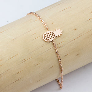 Rose gold pineapple bracelet from Kelabu shown on wooden cylinder