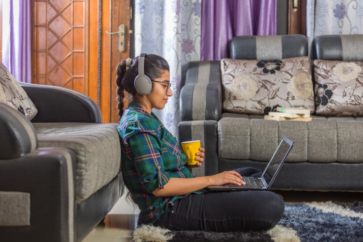 A high school student wearing headphones sits cross-legged on the floor in her living room holding a laptop and a coffee cup.