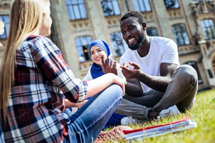 Three students in a study group sit on the lawn of a school campus talking.
