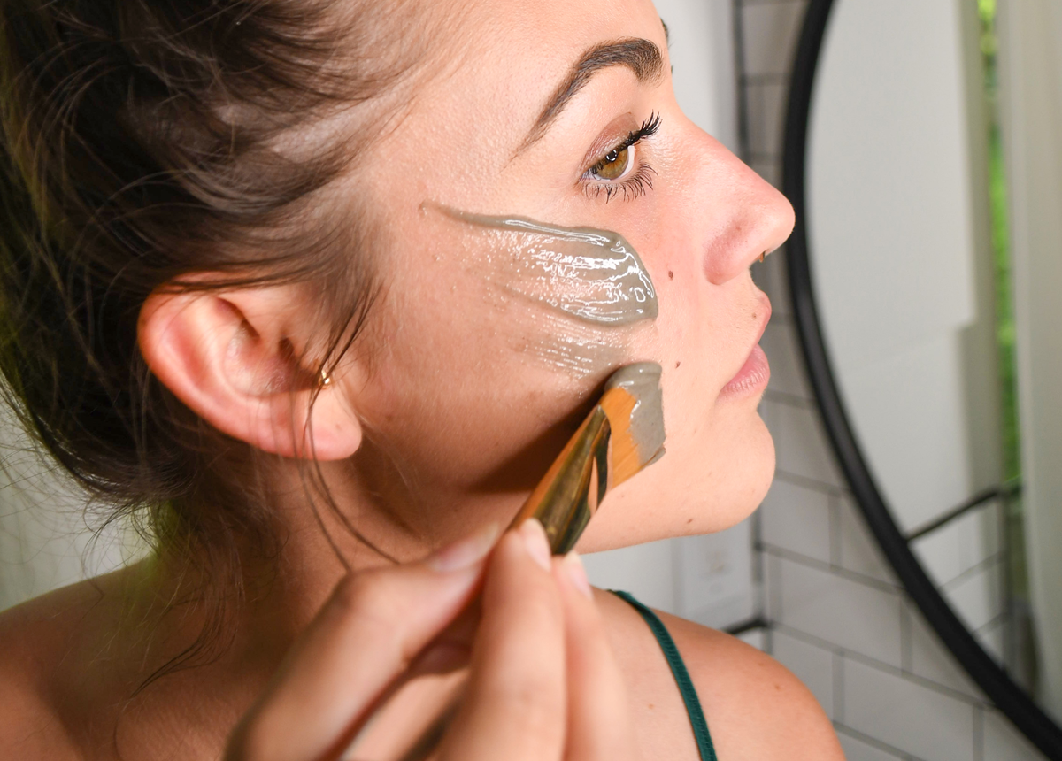 woman applying skin care facial mask to help with horonal acne