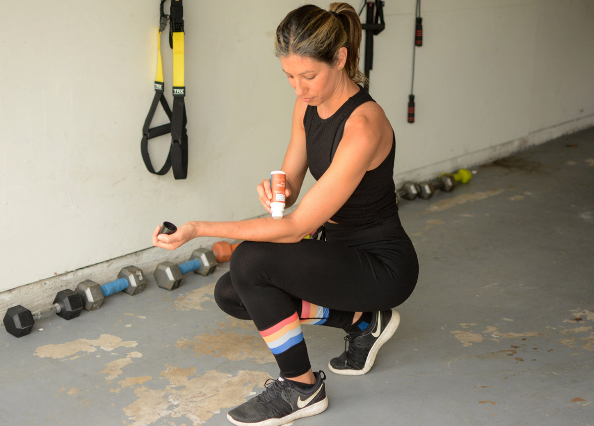 Woman applying natural sports balm after a workout