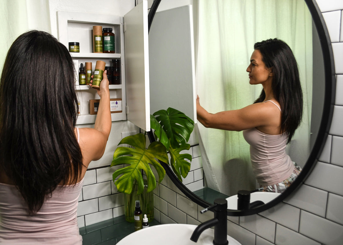 Woman getting Source Vitál  products out of Beauty Cabinet