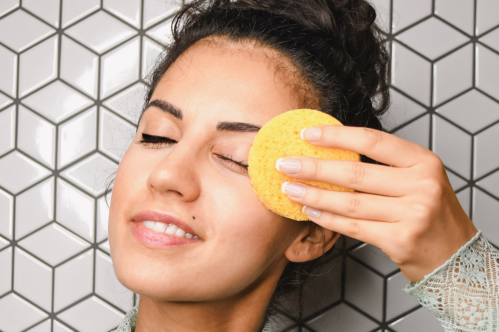 Woman removing eye makeup with source vital cleanser and sponge