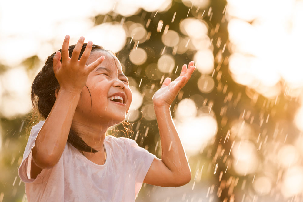 Little girl playing in the rain - afternoon rain essential oil blend by source vital apothecary