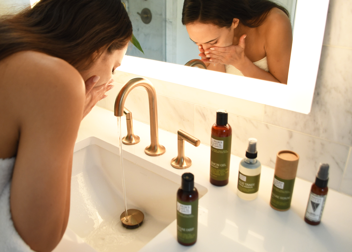 woman washing face as part of natural skin care routine