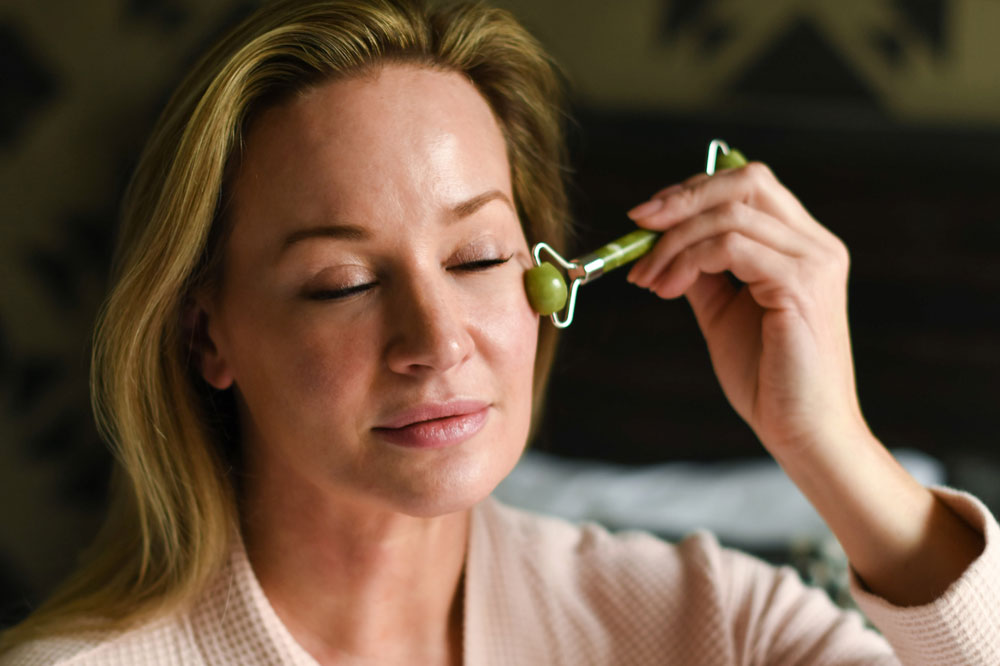 Woman using jade facial roller on eye area