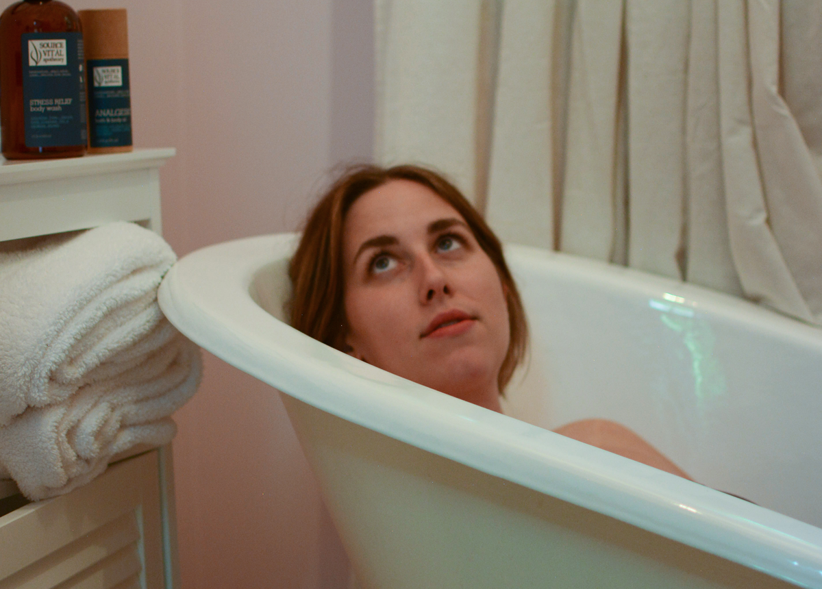woman enjoying relaxing bath with source vital products