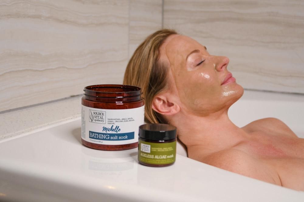 Woman taking a relaxing aromatherapy bath with custom made bath salts by Source Vital
