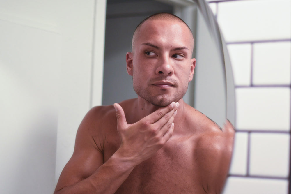 Muscular Man looks in Mirror at his skin