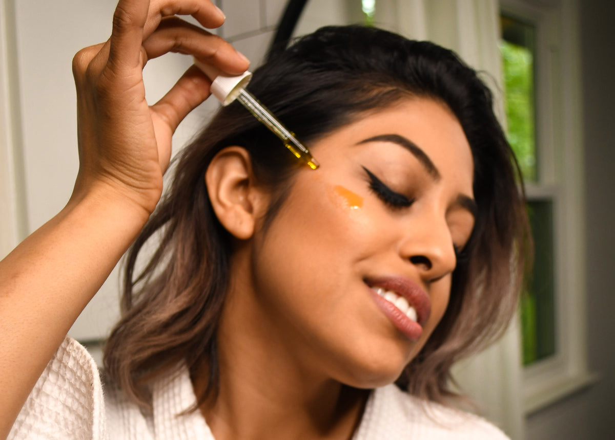 Woman drops botanical oil on her cheek