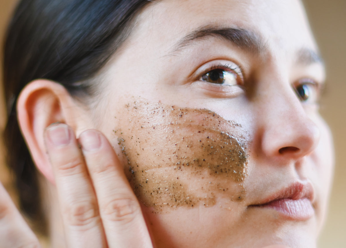 woman applies exfoliant to cheek