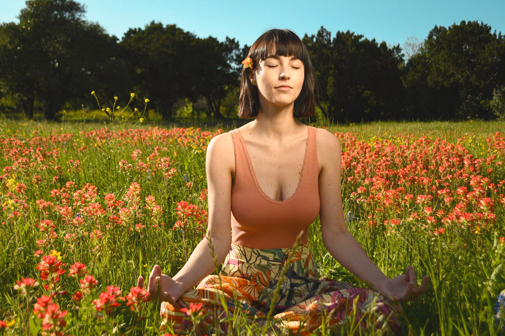 Woman meditating in wildflowers - self-care by source vital
