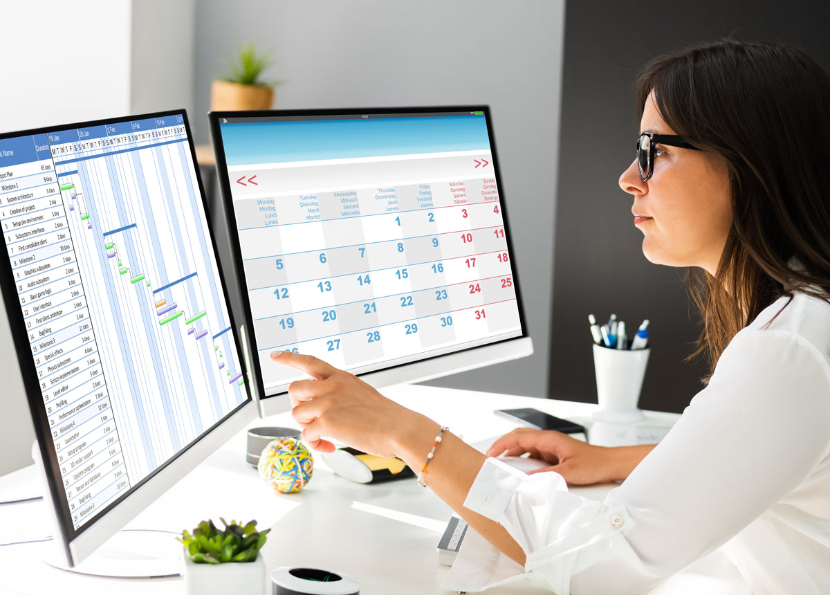 Woman working at home from multiple computer screens