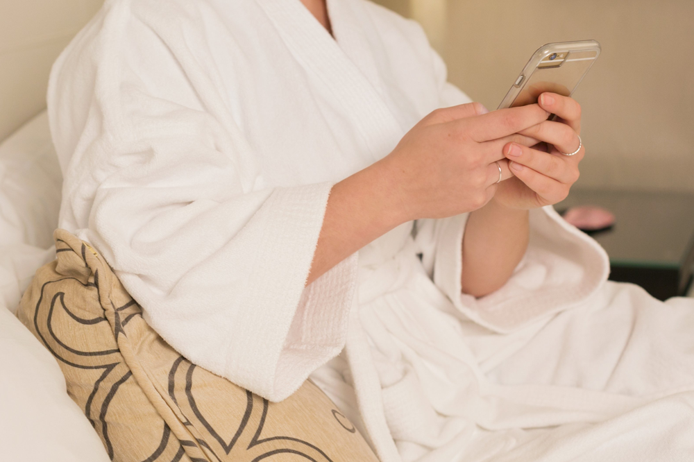 Woman in bed with cell phone
