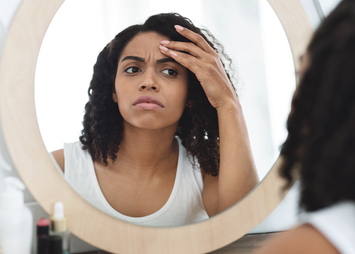 woman looks in the mirror to check for skin damage