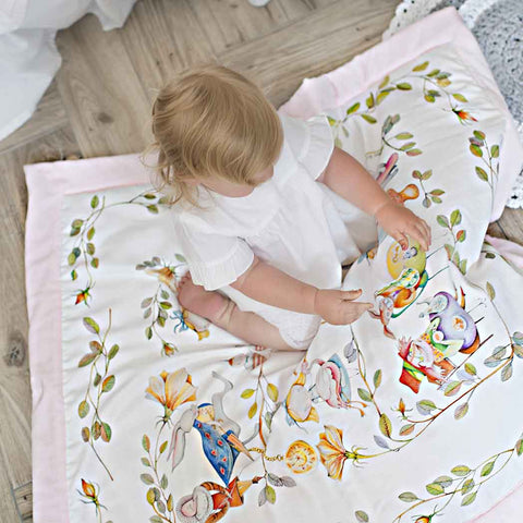 a baby girl playing on alice in wonderland cotton blanket