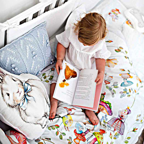 a baby girl reading a book in a cot with Alice in wonderland bed linen