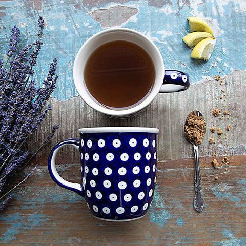 hand-decorated coffee tea mugs polka dots design on wooden table with a spoon and flowers