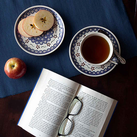 coffee tea cup and dessert plate from collection 864 on a table with a book and apples