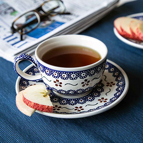 hand-decorated tea cup apple and strait times newspaper on blue tablecloth