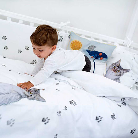 a boy in a cot with puss in boots bed linen