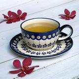 FLORAL PEACOCK HAND-DECORATED COFFEE TEA CUP WITH SAUCER ON A WOODEN WHITE TABLE WITH RED ORCHIDS